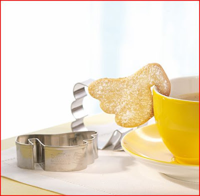 cookie cutter angel wing hanging off of a yellow mug