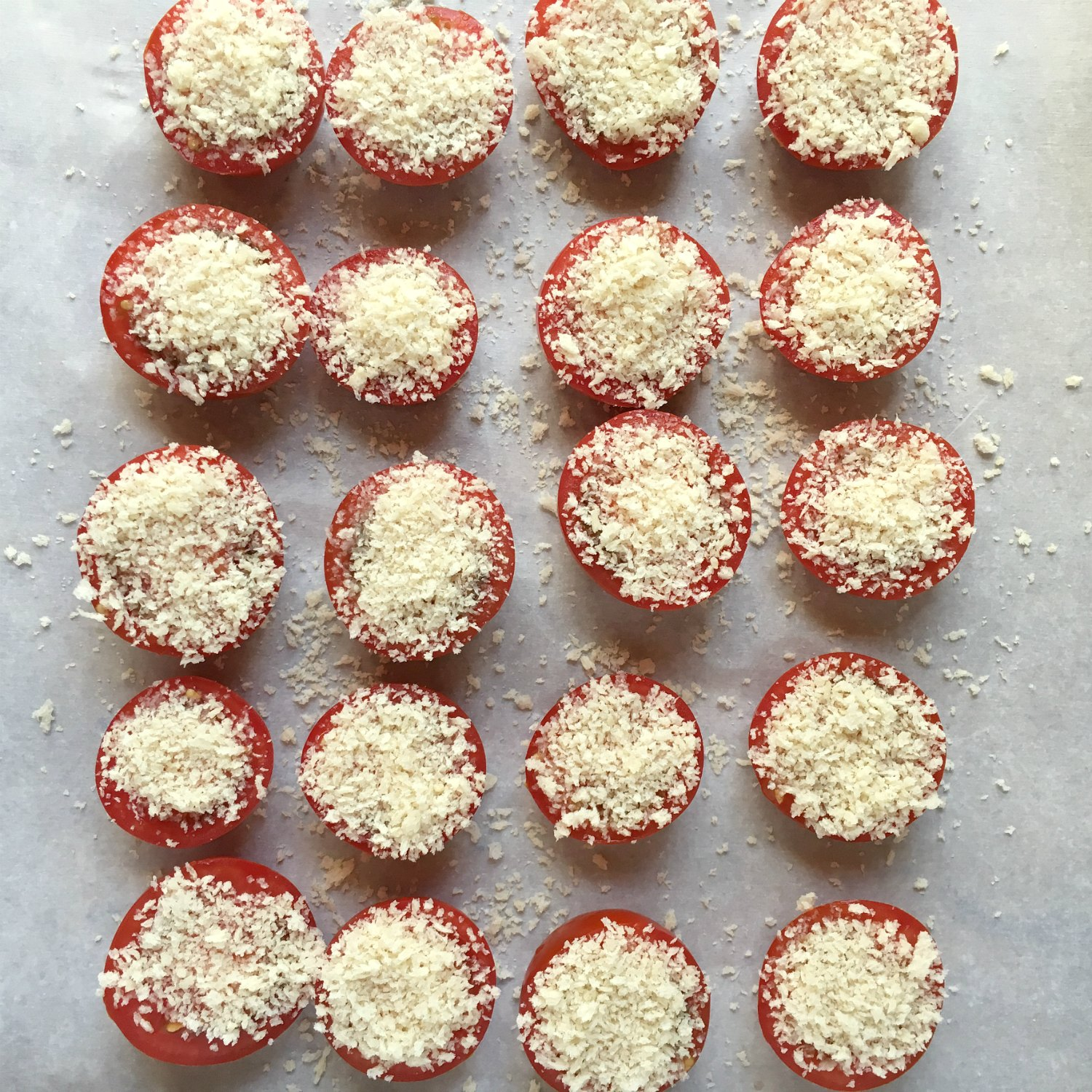 campari tomato halves on parchment paper topped with parmesan and panko bread crumbs panko parmesan tomatoes
