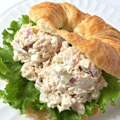 tuna salad sandwich with lettuce on croissant